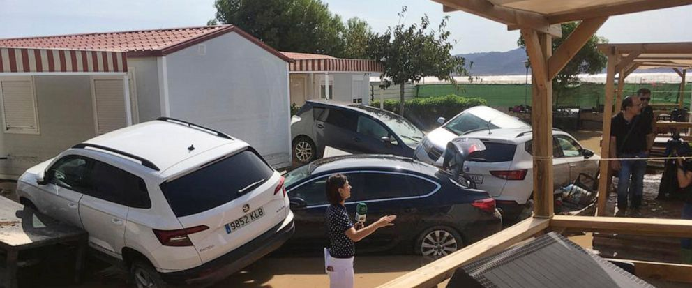 A TV reporter reports from a flooded campsite in the Cabo de Gata area, near Ruescas, Almeria in south-eastern Spain, Friday Sept. 13, 2019. Spanish authorities say that heavy storms in the southeast have claimed another victim, bringing the death to