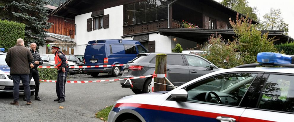 A police car is parked in front of a house in Kitzbuehl, Austria, Sunday, Oct. 6, 2019. Austrian police say a 25-year-old mans in custody after allegedly killing his ex-girlfriend, her family, and her new boyfriend in the Alpine resort town of Kitzb