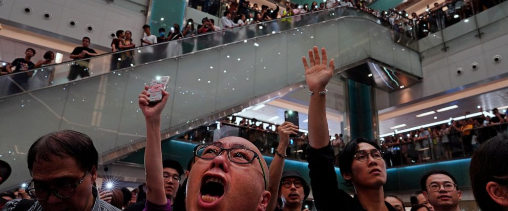 """Local residents sing a theme song written by protesters """"Glory be to thee"""" at a shopping mall in Hong Kong Wednesday, Sept. 11, 2019. Hundreds of Hong Kong citizens gathered at several malls late Wednesday, chanting slogans and belting out a new prot"""