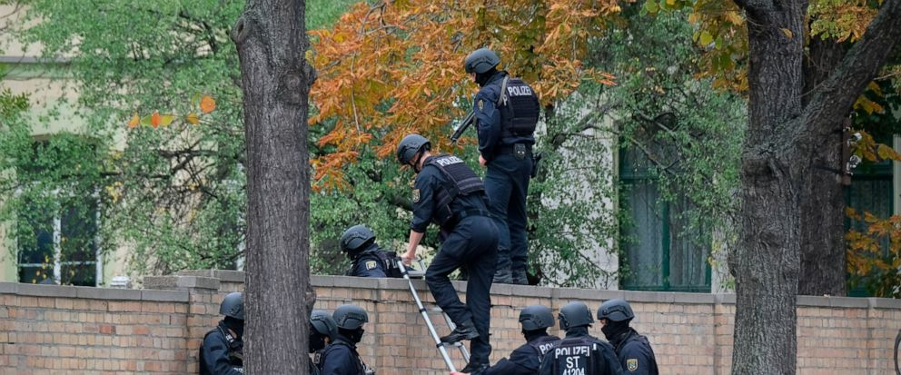 Police officers cross a wall at a crime scene in Halle, Germany, Wednesday, Oct. 9, 2019. A gunman fired several shots on Wednesday in the German city of Halle. Police say a person has been arrested after a shooting that left two people dead. (Sebast