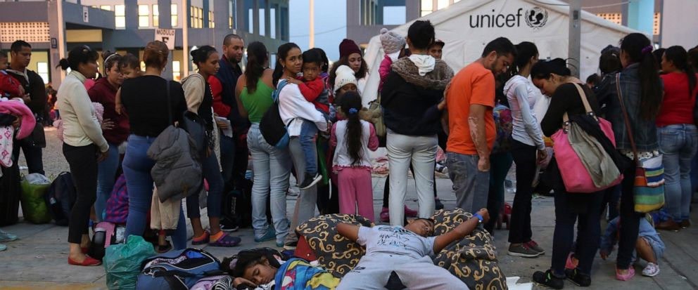 Venezuelan migrants rest while another group stands in line to enter am immigration office in Tumbes, Peru, Friday, June 14, 2019. Venezuelan citizens are rushing to enter Peru before the implementation of new entry requirements on migrants fleeing t