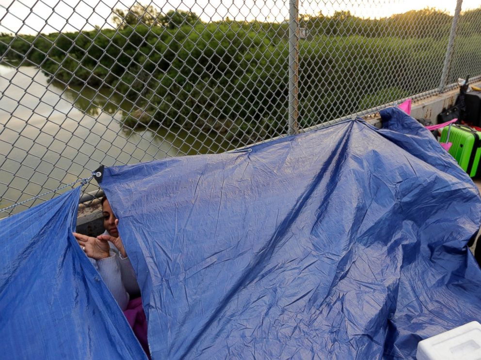Maidelen Gonzales, an immigrant from Honduras seeking asylum in the United States, waits under a tarp on the Brownsville and Matamoros International Bridge, Friday, Nov. 2, 2018, in Matamoros, Mexico.