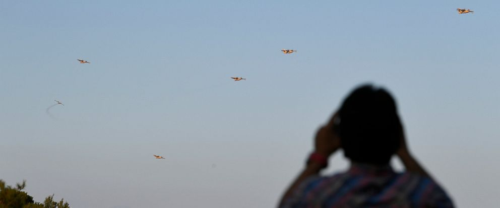 Airplanes operate during a wildfire as man takes photographs near Halkida town on the Greek island of Evia, Wednesday, Aug. 14, 2019. More than a thousand firefighters battled wildfires Tuesday in Greece, with the largest burning out of control throu