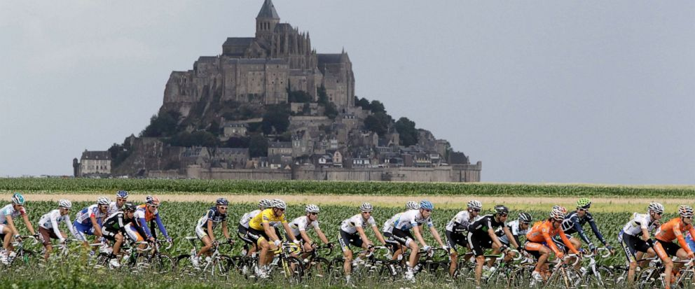 FILE - In this Thursday July 7, 2011 file photo, the pelaton passes the world heritage site Mont Saint-Michel, a rocky tidal island which holds a monastery, during he sixth stage of the Tour de France cycling race. Monuments are the emotional backbon
