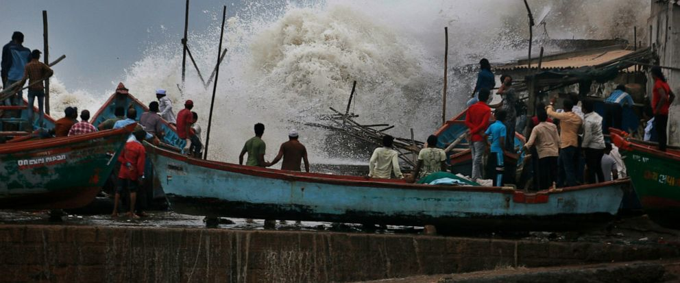 A waves crashes as people stand on boats on the Arabian Sea coast in Veraval, Gujarat, India, Wednesday, June 12, 2019. Indian authorities evacuated tens of thousands of people on Wednesday as a severe cyclone in the Arabian Sea approached the wester