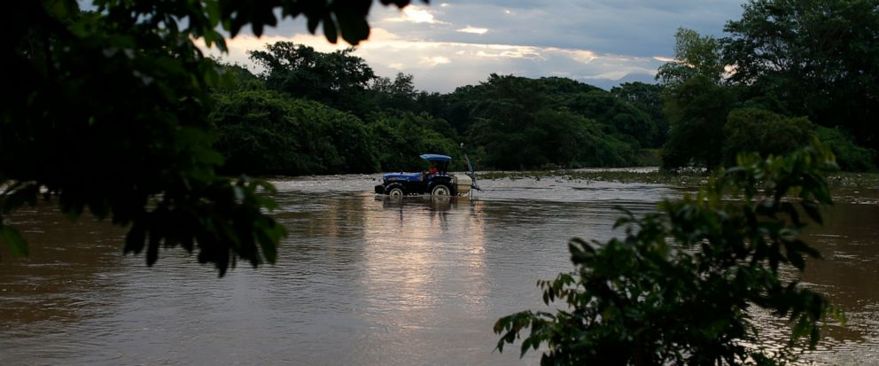 A man drives a tractor through the Suchiate river from Frontera Hidalgo, Mexico, toward Guatemala, where a handful of local farmers graze their cattle, Thursday, June 13, 2019. Such crossings are part of daily life in the border town of Frontera Hida
