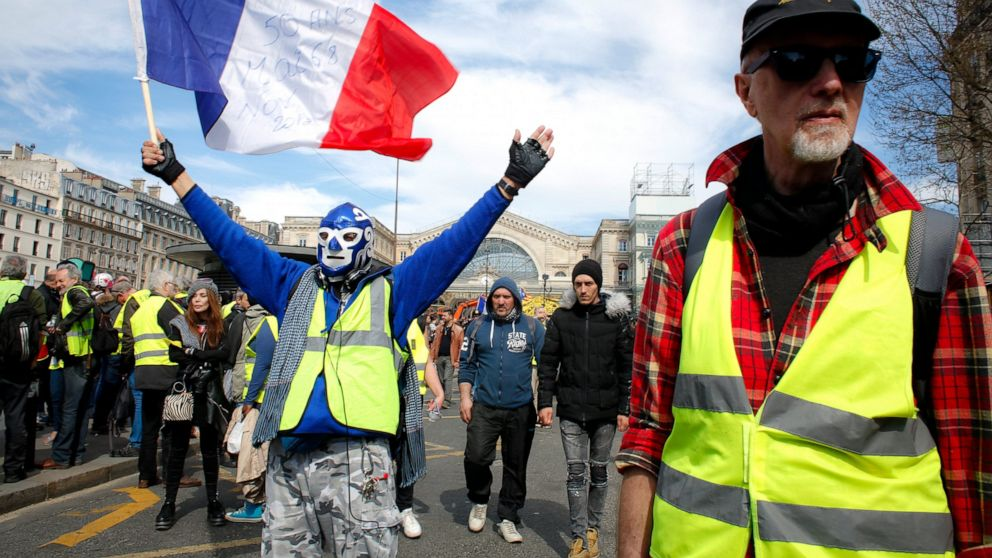 A masked protester waves the French flag as French yellow vest protesters rally to support an older woman activist injured in a confrontation with police, Saturday, March 30, 2019, in Paris. The demonstrators are undeterred by protest bans or repeated injuries in 20 weeks of demonstrations, marching again Saturday in Paris, Bordeaux and other cities to keep pressing President Emmanuel Macron to do more to help working classes, redesign French politics _ or step down altogether. (AP Photo/Thibault Camus)