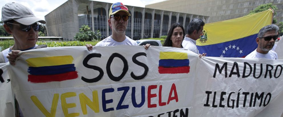 "Venezuelan citizens living in Brazil hold signs that read in Spanish ""S.O.S. Venezuela. Dont leave us alone,"" left, and ""Maduro. Illegitimate,"" during protest against the inauguration of Venezuelas President Nicolas Maduro outside Itamaraty Palace"