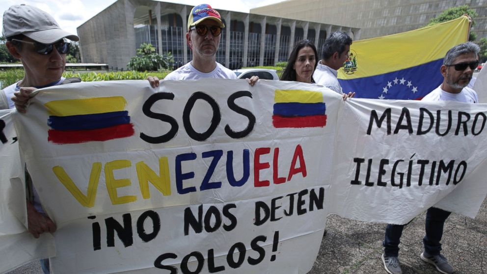 "Venezuelan citizens living in Brazil hold signs that read in Spanish ""S.O.S. Venezuela. Don't leave us alone,"" left, and ""Maduro. Illegitimate,"" during protest against the inauguration of Venezuela's President Nicolas Maduro outside Itamaraty Palace in Brasilia, Brazil, Thursday, Jan. 10, 2019. Maduro started a second, six-year term Thursday despite international cries urging him to step down and return democratic rule to a country suffering a historic economic implosion. (AP Photo/Eraldo Peres)"