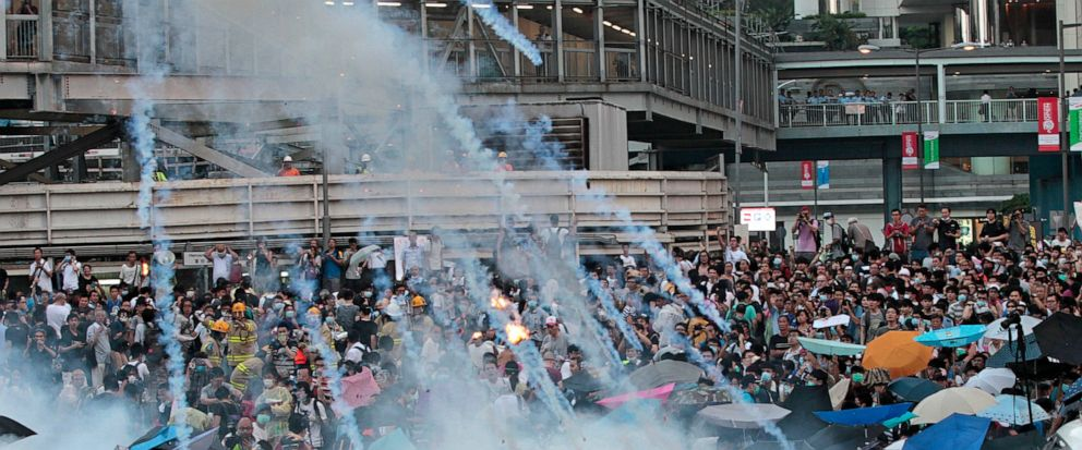In this Sunday, Sept. 28, 2014, file photo, riot police launch tear gas into the crowd as thousands of protesters surround the government headquarters in Hong Kong. Hong Kong police used tear gas on Sunday and warned of further measures as they tried