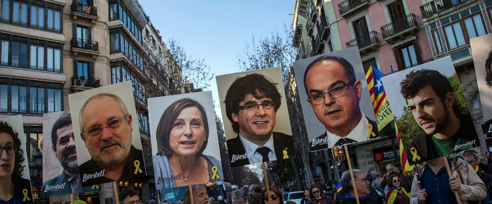 FILE - In this Saturday, Feb. 16, 2019 file photo, pro independence demonstrators hold photos of imprisoned and exiled pro-independence political leaders, during a demonstration in Barcelona, Spain. A dozen politicians and activists on trial for thei