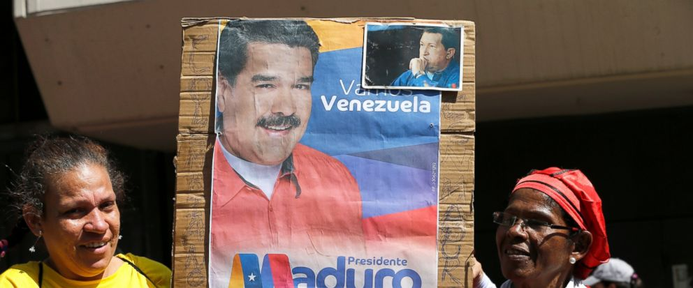 Supporters of Venezuelas President Nicolas Maduro hold a poster of him outside the Supreme Court where he is being sworn-in for another term in Caracas, Venezuela, Thursday, Jan. 10, 2019. Maduro was sworn in to a second term amid international call
