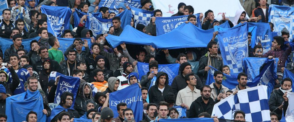 FILE - In this Dec. 9, 2011 file photo, supporters of Iranian soccer team Esteghlal, hold flags of their favorite team, at the Azadi (Freedom) stadium, in Tehran, Iran. Sahar Khodayari, an Iranian female soccer fan died after setting herself on fire