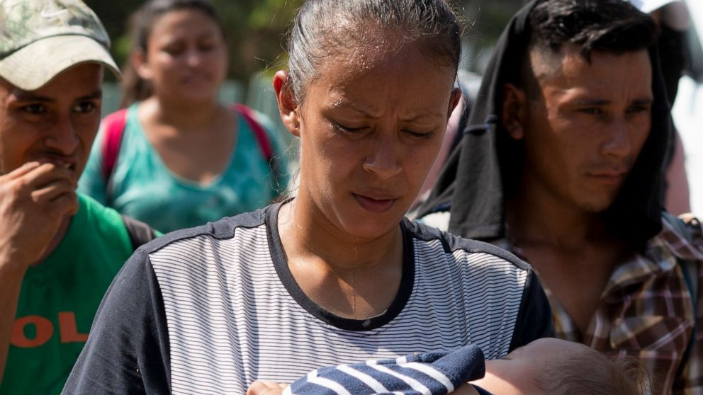 A migrants mother an child, part of the caravan hoping to reach the U.S. border, move on a road in Tapachula, Chiapas State, Mexico, Thursday, March 28, 2019. A caravan of about 2,500 Central Americans and Cubans is currently making its way through Mexico's southern state of Chiapas. (AP Photo/Isabel Mateos)