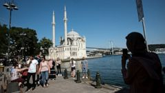 Tourists walk near Mecidiye Mosque and Bosporus Bridge in the background, in Istanbul, Monday, June 24, 2019, a day after Ekrem Imamoglu, the candidate of the secular opposition Republican People's Party, won the election for mayor of Istanbul. Imamo