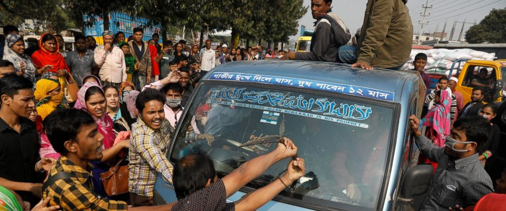Bangladeshi garment workers vandalize a vehicle during a protest in Savar, on the outskirts of Dhaka, Bangladesh, Wednesday, Jan. 9, 2019. Thousands of garment workers have staged demonstrations to demand better wages for the fourth straight day, shu
