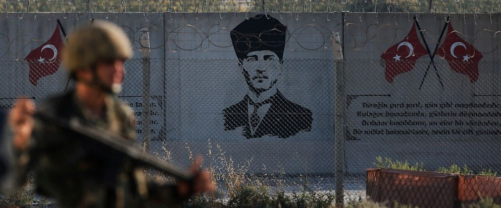 Shortly after the Turkish operation inside Syria had started and backdropped by a graffiti of modern Turkeys founder Mustafa Kemal Ataturk, a Turkish soldier stands on the Turkish side of the border in Akcakale, Sanliurfa province, southeastern Turk