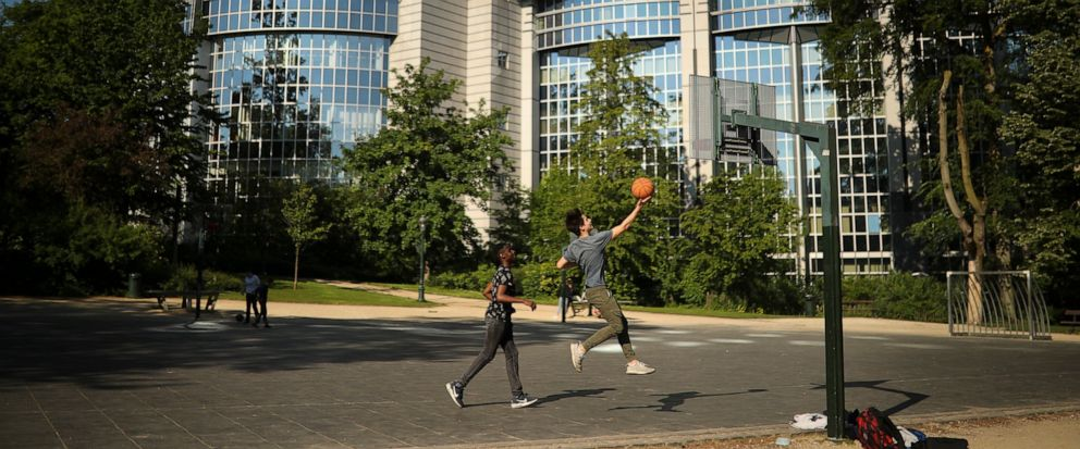 Youngsters play basketball in front of the European Parliament building in Brussels, Wednesday, May 15, 2019. Europeans from 28 countries will head to the polls May 23-26 to choose lawmakers to represent them at the European Parliament for the next f