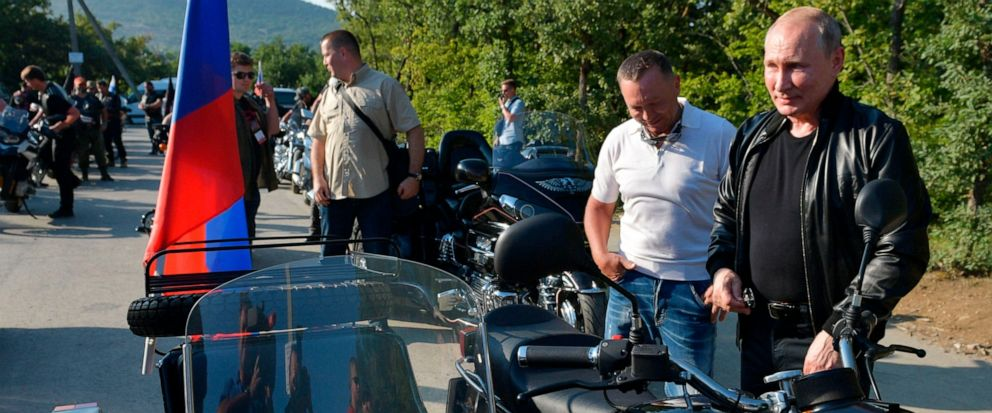 "Russian President Vladimir Putin, right, looks at a Russia made ""Ural"" motorbike during the Babylons Shadow bike show camp near in Sevastopol, Crimea, Saturday, Aug. 10, 2019. (Alexei Druzhinin, Sputnik, Kremlin Pool Photo via AP)"