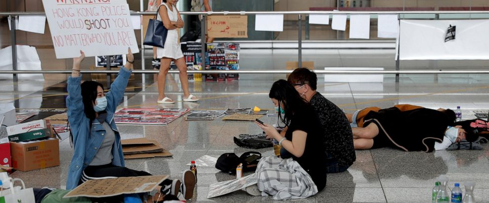 A protester shows a placard to travellers as they continue their sit-in rally at the airport in Hong Kong, Wednesday, Aug. 14, 2019. Flight operations resumed at the airport Wednesday morning after two days of disruptions marked by outbursts of viole