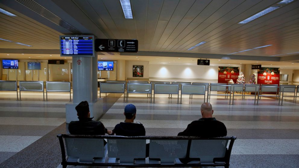 People wait at the almost empty arrival hall of the Rafik Hariri International Airport during a strike in Beirut, Lebanon, Friday, Jan. 4, 2019. Parts of Lebanon's public and private sectors have gone into a strike called for by the country's labor unions to protest worsening economic conditions and months of delays in the formation of a new government. (AP Photo/Bilal Hussein)