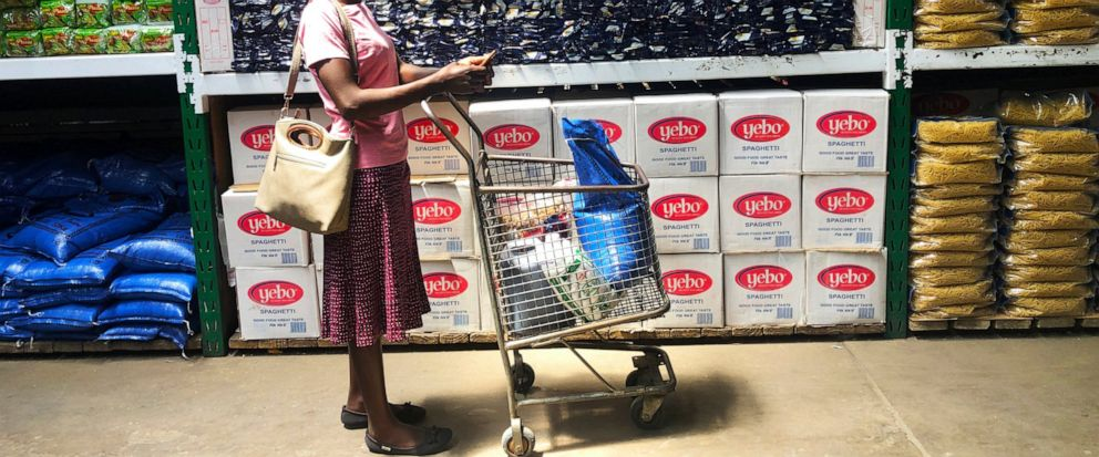 A woman does a quick calculation on her phone before buying groceries at a shop in Harare, in this Wednesday, Oct, 9, 2019 photo. Hyperinflation is changing prices so quickly in the southern African nation that what you would see displayed on a super