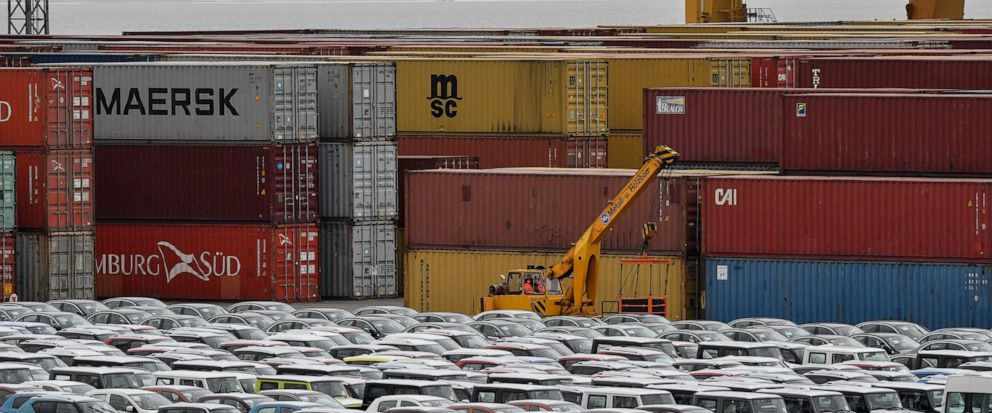 FILE - In this Thursday, May 16, 2019 photo cars for export and import are stored in front of containers at the harbor in Bremerhaven, Germany. The German economy shrank by 0.1 percent in the second quarter as global trade conflicts and troubles in t