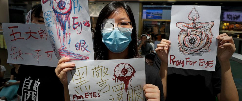 """People hold signs which read """" Black Police, Return eye,"""" bottom center, during a protest at the arrival hall of the Hong Kong International airport in Hong Kong, Monday, Aug. 12, 2019. It is reported that police shot a woman in the eye with a projec"""