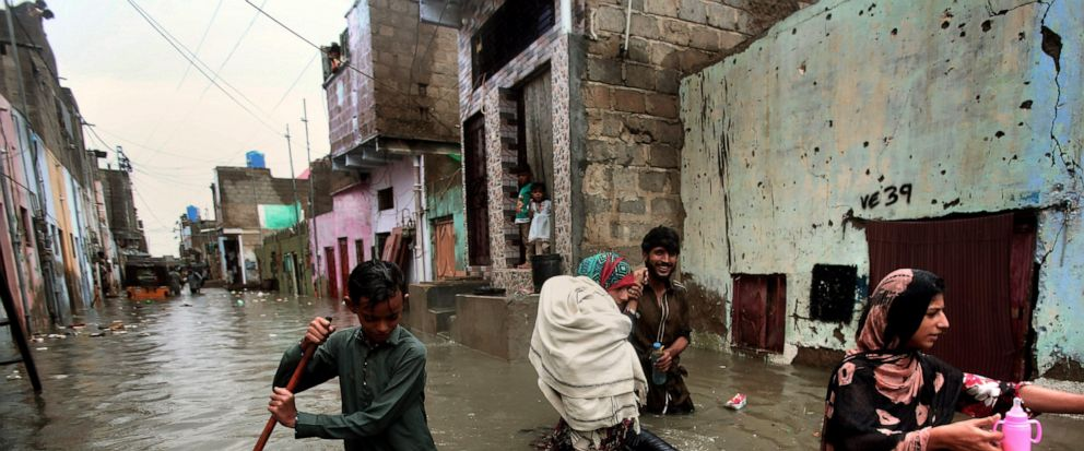 A family wades through a flooded street caused by heavy monsoon rains, in Karachi, Pakistan, Sunday, Aug. 11, 2019. Monsoon rains have inundated much of Pakistan, leaving large parts of the southern city of Karachi underwater and causing some deaths.