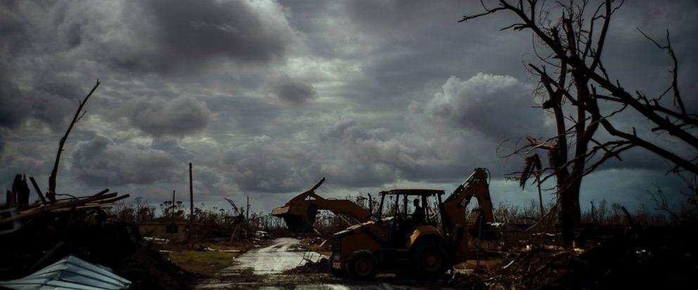 Mos Antenor, 42, drives a bulldozer while clearing the road after Hurricane Dorian Mcleans Town, Grand Bahama, Bahamas, Friday Sept. 13, 2019. (AP Photo/Ramon Espinosa)