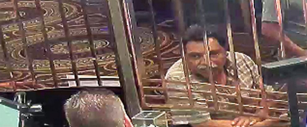 In this July 30, 2018 photo provided by the U.S. Attorneys Office in Detroit Juan Garcia-Jimenez right exchanges money at Caesars casino in Windsor, Ontario, Canada, before taking two men to an international railroad tunnel under the Detroit River.