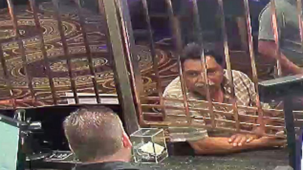 In this July 30, 2018 photo provided by the U.S. Attorney's Office in Detroit Juan Garcia-Jimenez right exchanges money at Caesars casino in Windsor, Ontario, Canada, before taking two men to an international railroad tunnel under the Detroit River. Garcia-Jimenez was sentenced to 16 months in prison Monday, April, 15, 2019, for helping immigrants try to illegally enter the U.S. The tunnel is used by cargo trains moving between Ontario, Canada, and the U.S. (U.S. Attorney's Office in Detroit via AP)