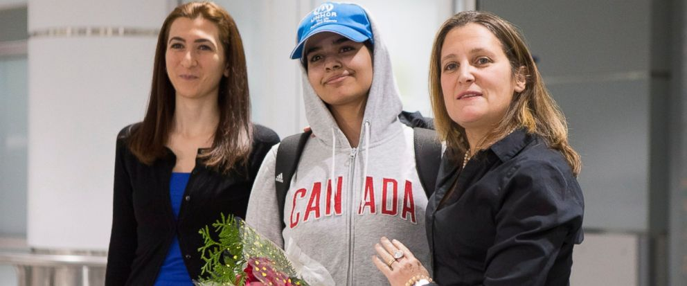 Rahaf Mohammed Alqunun, 18, center, stands with Canadian Minister of Foreign Affairs Chrystia Freeland, right, as she arrives at Toronto Pearson International Airport, on Saturday, Jan.12, 2019. The Saudi teen fled her family while visiting Kuwait an