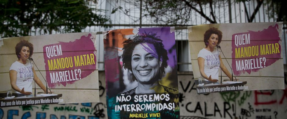 """Posters showing councilwoman Marielle Franco with messages that read in Portuguese: """"Who ordered the killing of Marielle,"""" and """"We will not be stopped,"""" are displayed at the site where Franco was gunned down, during a demonstration marking the one ye"""