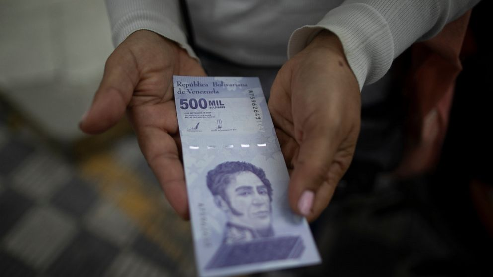 FILE - In this March 16, 2021 file photo, a woman shows a new 500,000 Bolivar bill after withdrawing it from a bank in Caracas, Venezuela, after the Central Bank of Venezuela (BCV) launched three new banknotes to increase the highest denomination of
