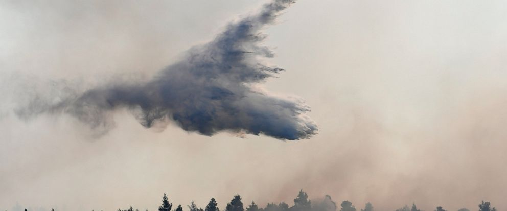 An airplane drops water over a wildfire near Halkida town on the Greek island of Evia, Wednesday, Aug. 14, 2019. More than a thousand firefighters battled wildfires Tuesday in Greece, with the largest burning out of control through a nature reserve o