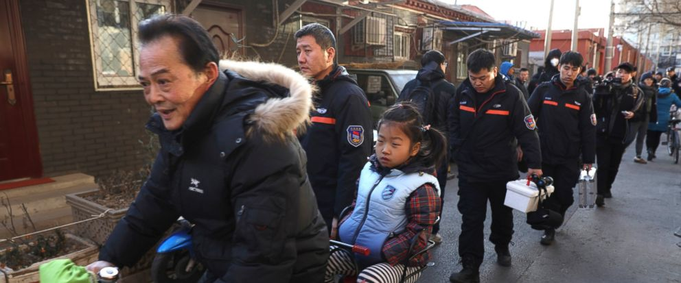 A man rides with a student pass crime scene investigators as they leave the Beijing No. 1 Affiliated Elementary School of Xuanwu Normal School in Beijing, China, Tuesday, Jan. 8, 2019. A male attacker injured 20 children Tuesday inside the primary sc