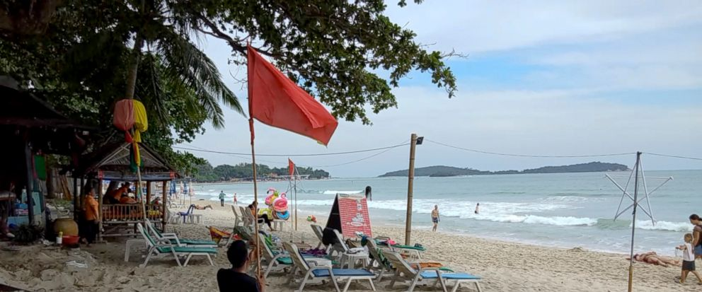 A man raises a red flag indicating rough weather conditions in Chaweng beach, Koh Samui, Thailand, Thursday, Jan. 3, 2019. Thai weather authorities are warning that a tropical storm will bring heavy rains and high seas to southern Thailand and its fa