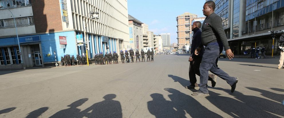 People walk past armed riot police ahead of a planned protest in Harare, Friday, Aug. 16, 2019. Zimbabwes police patrolled the streets of the capital Friday morning while many residents stayed home fearing violence from an anti-government demonstrat