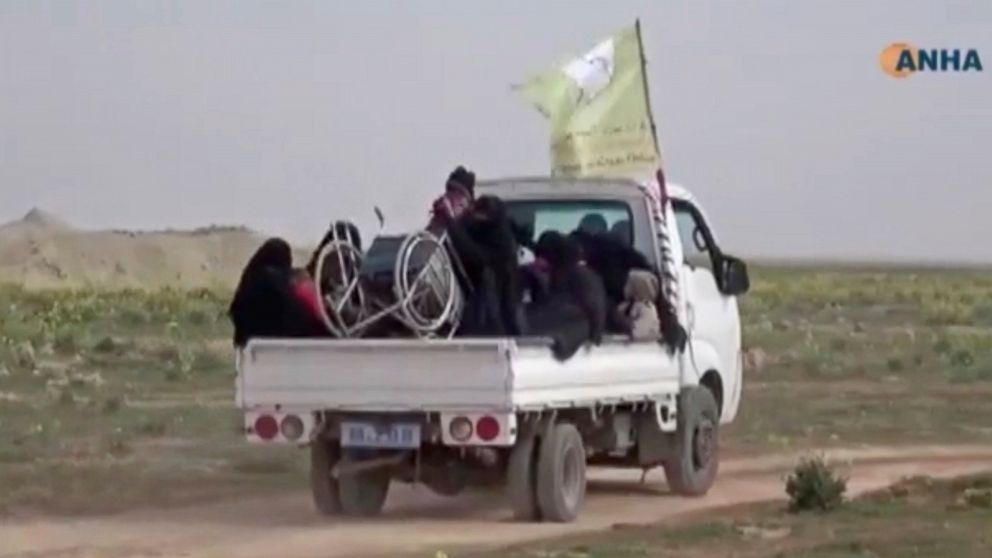 """In this Sunday, Feb. 10, 2019 image from video provided by Hawar News Agency, ANHA, an online Kurdish news service, civilians flee fighting near Baghouz, Syria. Fierce fighting was underway Monday between U.S.-backed Syrian forces and the Islamic State group around the extremists' last foothold in eastern Syria. The capture of the IS-held village of Baghouz and nearby areas would mark the end of a four-year global war to end IS' territorial hold over large parts of Syria and Iraq, where the group established its self-proclaimed """"caliphate"""" in 2014. (ANHA via AP)"""