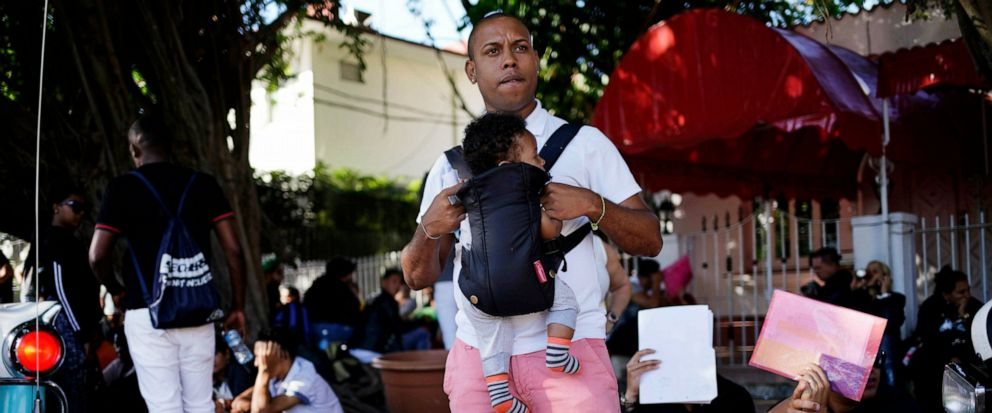 In this April 26, 2019, photo, a man holds his baby while he waits his turn to enter Nicaraguas embassy to apply for travel visas for him and his son to Nicaragua, in Havana, Cuba. The surge over the past several months has been propelled in part by