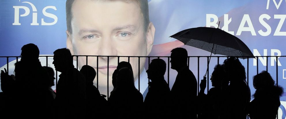 In this photo taken Thursday Sept. 26, 2019 supporters of Polands ruling right-wing party are standing in line before a candidates billboard to get to a party convention in Warsaw, Poland, ahead of Sunday parliamentary election in which the Law and