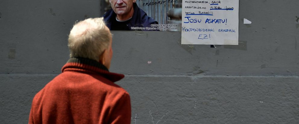 A man looks at a poster with the face of Basque separatist militant Josu Ternera, in his home town of Ugao-Miraballes, Spain, Thursday, May 16, 2019. The most wanted member of the Basque separatist militant group ETA who had been on the run for 17 ye