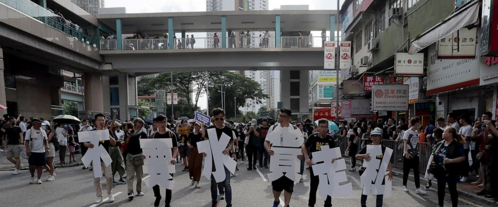 """Protesters hold up words that read: """"Against smuggling grey goods"""" in Hong Kong Saturday, July 13, 2019. Several thousand people are marching in Hong Kong against traders from mainland China in what is fast becoming a summer of unrest in the semi-aut"""