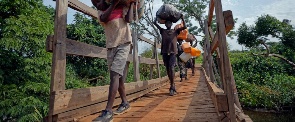 FILE - In this Thursday, June 8, 2017 file photo, from left, South Sudanese refugees Thomas Wani, 12, brother Peter Lemi, 14, mother Rose Sunday, and father Julius Lezu, cross a wooden bridge from South Sudan to Uganda at the Busia crossing, near Kul