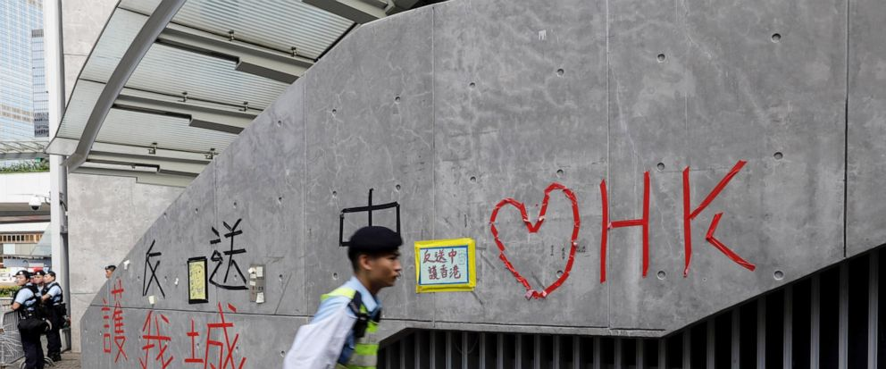 """A police officer passes by """"Love Hong Kong"""" words formed with tape near the Legislative Council in Hong Kong on Friday, June 14, 2019. Calm appeared to have returned to Hong Kong after days of protests by students and human rights activists opposed t"""