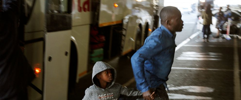 Nigerians exit a bus at the O.R. Tambo International Airport in Johannesburg, South Africa, Wednesday, Sept. 11, 2019. A group of Nigerians boarded a free flight from Johannesburg to Lagos on Wednesday, following a week of violence targeting foreigne