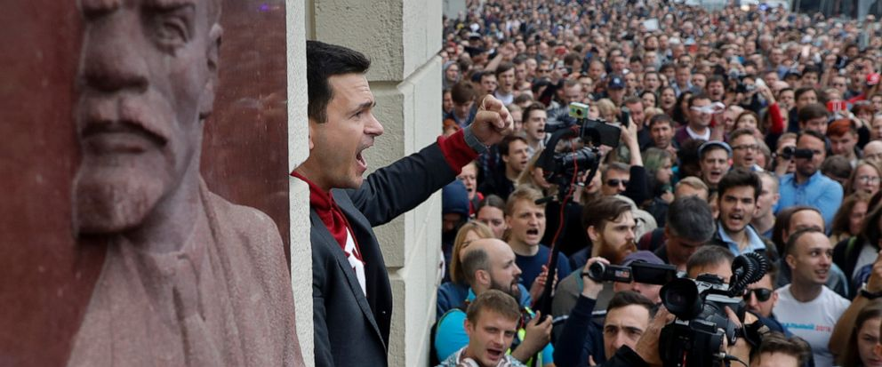 Russian opposition candidate Russian and activist Ilya Yashin, center, gestures while speaking to a crowd next to a bas-relief of the Soviet founder Vladimir Lenin, left, during a protest in Moscow, Russia, Sunday, July 14, 2019. Opposition candidate