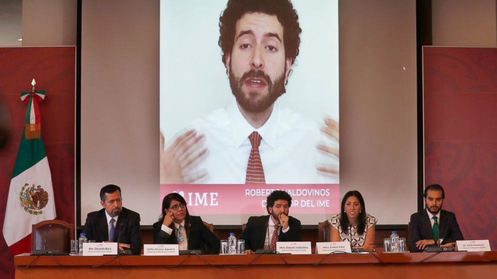 Roberto Valdovinos, head of the Institute for Mexicans Abroad, is shown speaking in a video behind as he gives a news conference, sitting center, in Mexico City, Thursday, March 14, 2019. The Mexican government is launching open-ended public consultation forums in the U.S. to give Mexicans living there a chance to opine on Mexico's national development plan. (AP Photo/Marco Ugarte)