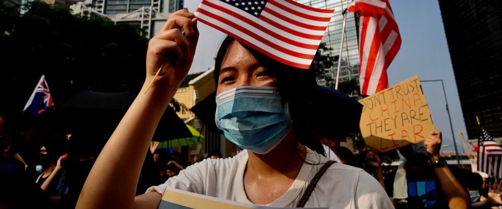 Protesters wave U.S. flags and shout slogans as they march from Chater Garden to the U.S. c\Consulate in Hong Kong, Sunday, Sept. 8, 2019. Demonstrators in Hong Kong plan to march to the U.S. Consulate on Sunday to drum up international support for t